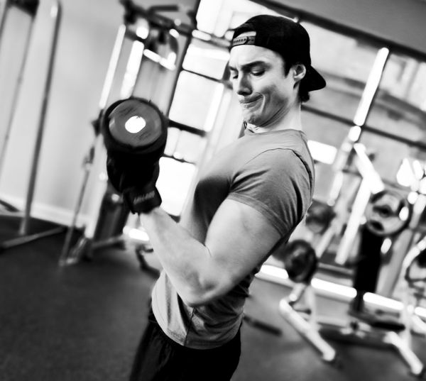Side View Of Determined Man Lifting Dumbbell At Gym
