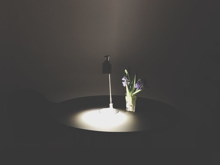 Close-up of illuminated flower vase on table at home