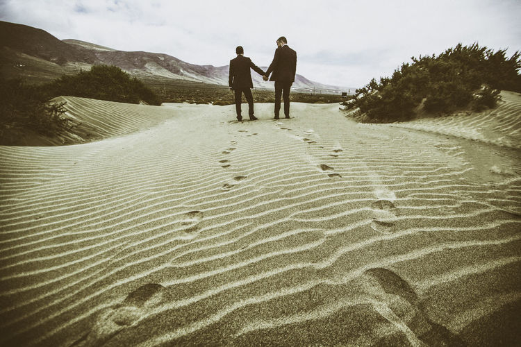 Rear View Of Gay Men Holding Hands While Standing On Sand At Desert Against Sky