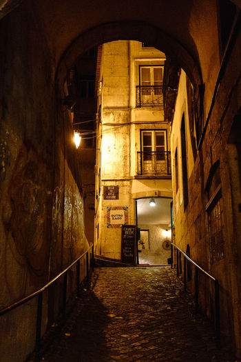 Empty alley amidst buildings in city at night