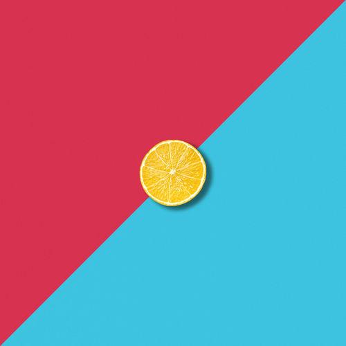 Directly above shot of lemon slice on colored background