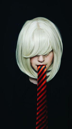 Mid Adult Woman With Tie In Mouth Against Black Background
