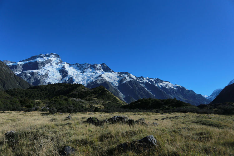 Scenic view of mt cook by field against clear blue sky
