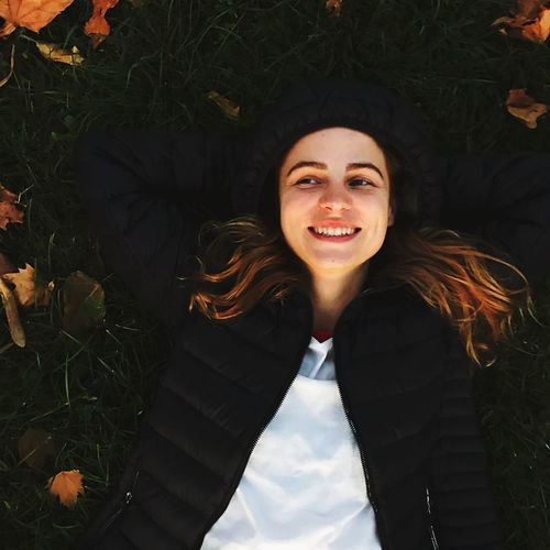 High Angle View Of Smiling Young Woman Looking Away While Lying On Field At Park During Autumn