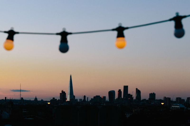 Light bulbs hanging against shard london bridge during sunset