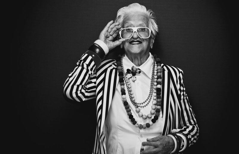 Portrait of smiling senior woman wearing eyeglasses against black background