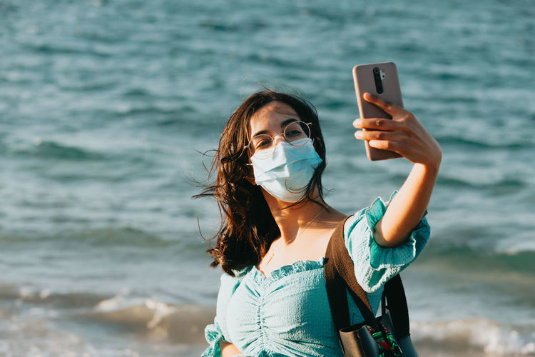 Young woman using mobile phone in sea