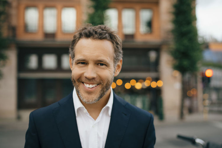 Portrait of smiling mid adult man in city