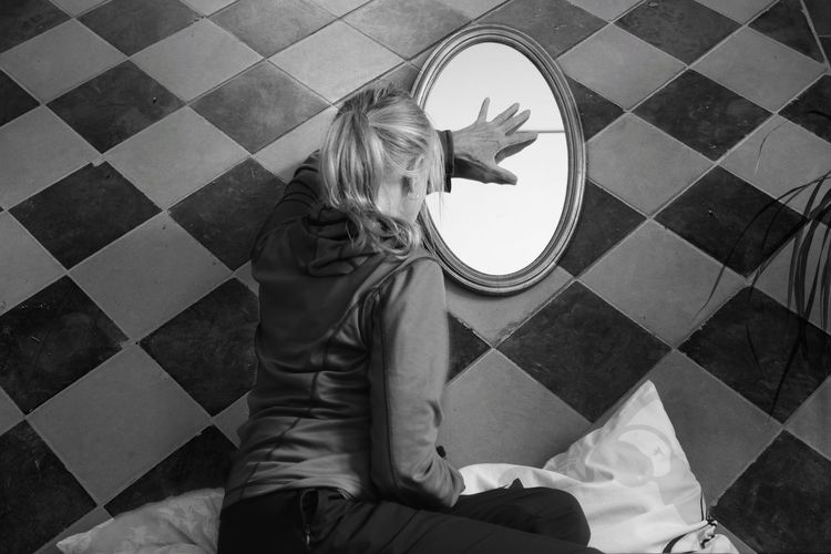 Rear view of woman touching mirror on floor