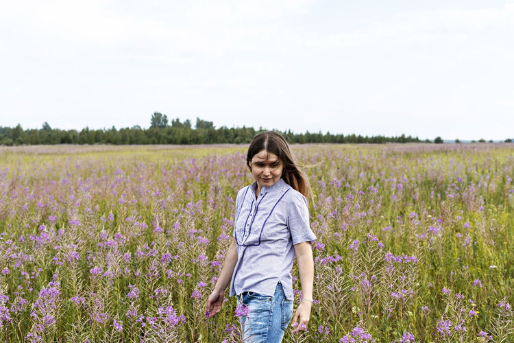 Young beautiful smiling blond woman in purple shirt walking in meadow among flowers fireweed,  field
