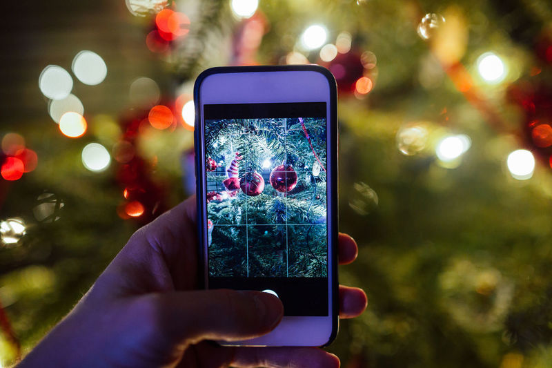 Close-Up Of Hand Photographing Christmas Tree At Night