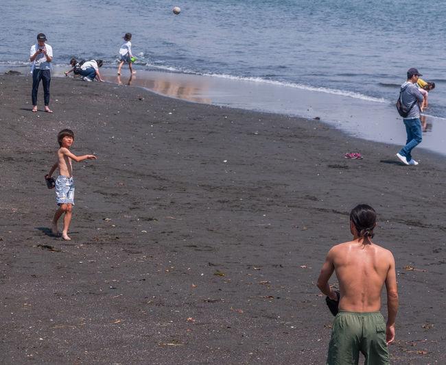 Rear view of shirtless men on beach