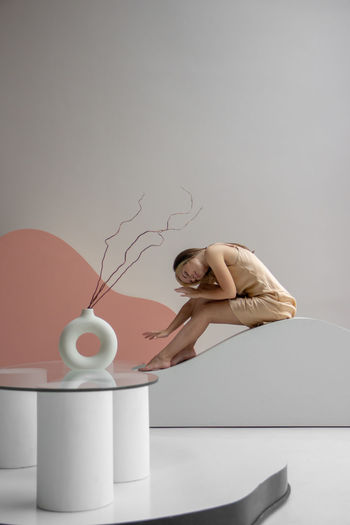 Side view of woman on white table against wall