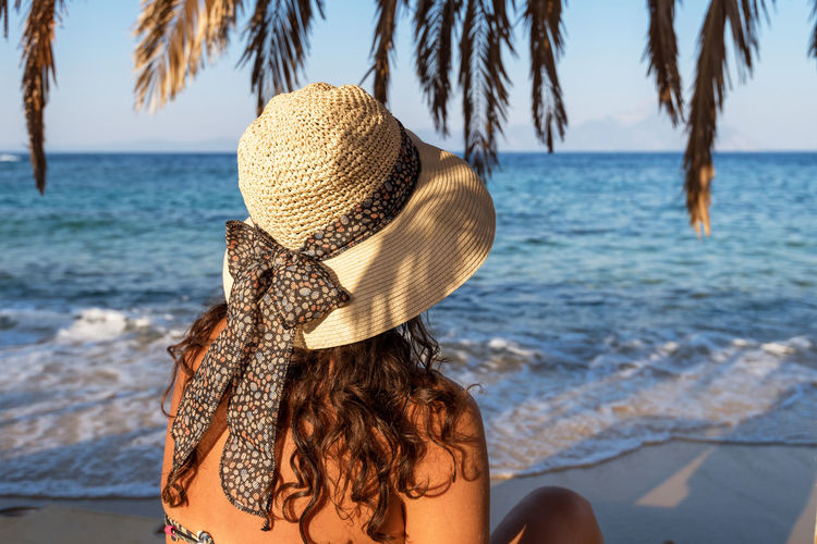 Rear view of woman in hat at beach