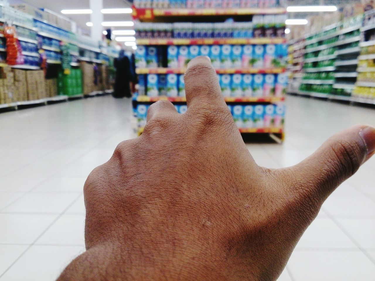 Cropped image of hand gesturing in supermarket