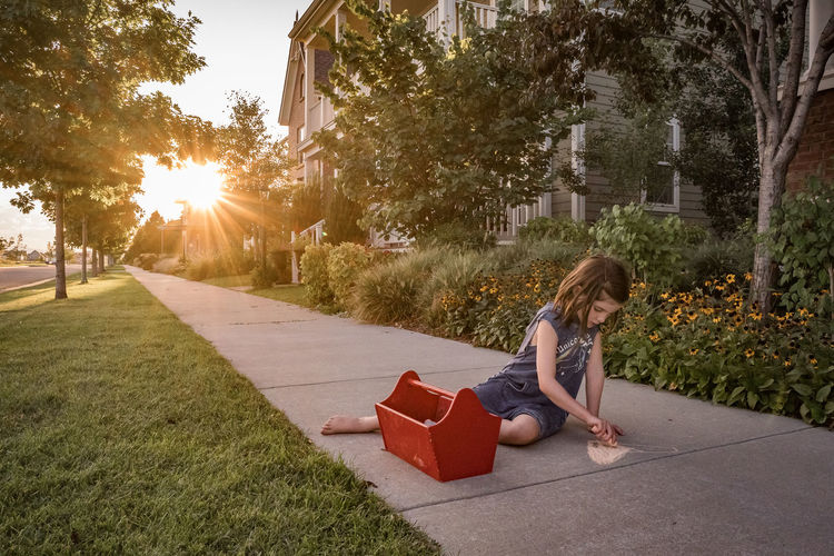 Woman sitting on grass in city