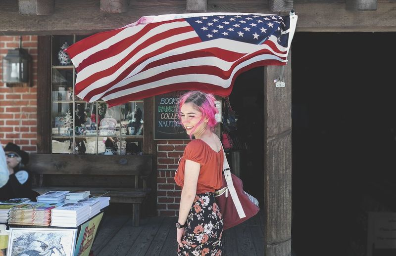 Side View Of Smiling Woman Standing By American Flag In City