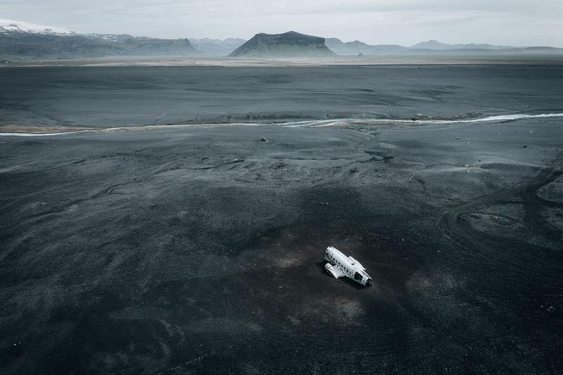 Cinematic aerial view of dc-3 airplane wreckage at black beach, sólheimasandur, iceland.