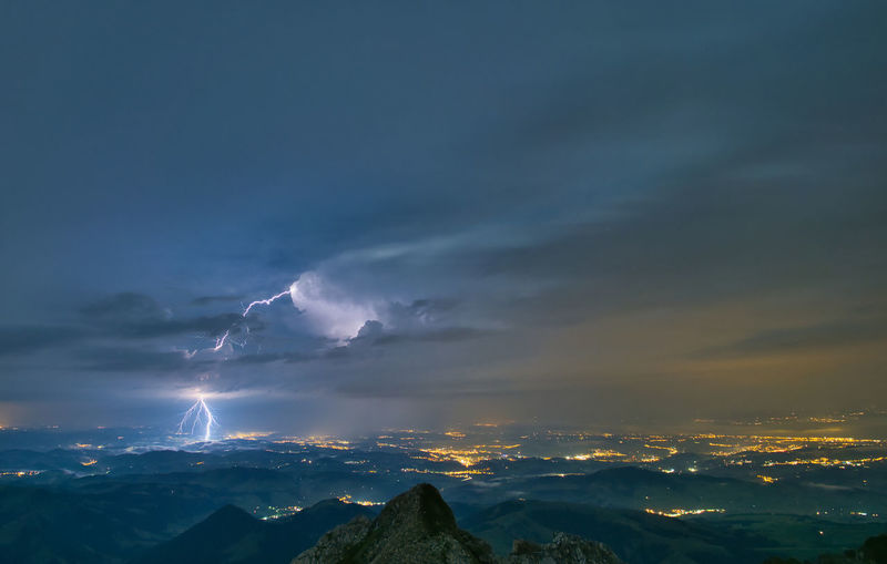 Scenic view of mountains against night sky during thunderstorm