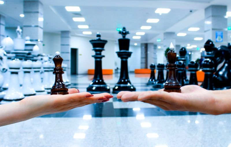 Cropped hands of friends holding chess pieces over floor