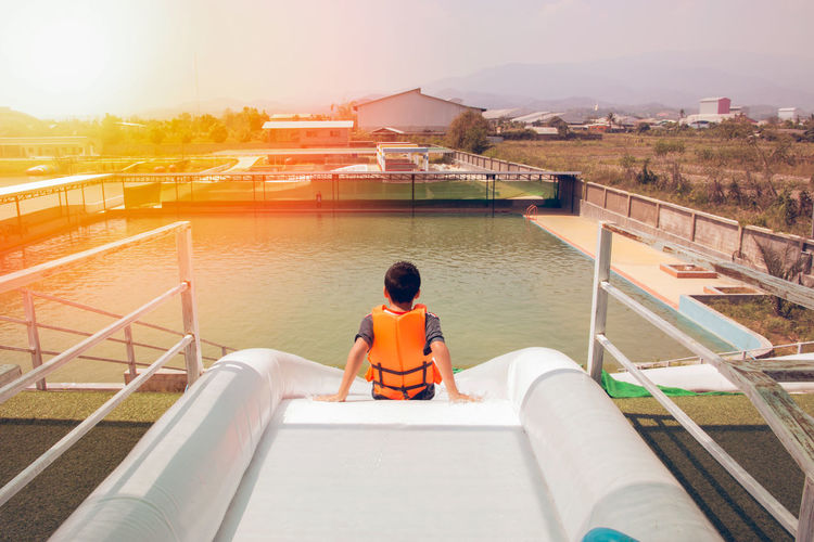 Rear view of boy sitting on water slide