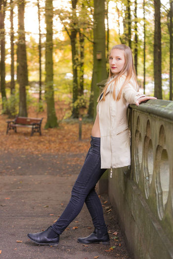 Portrait of girl standing by wall in park