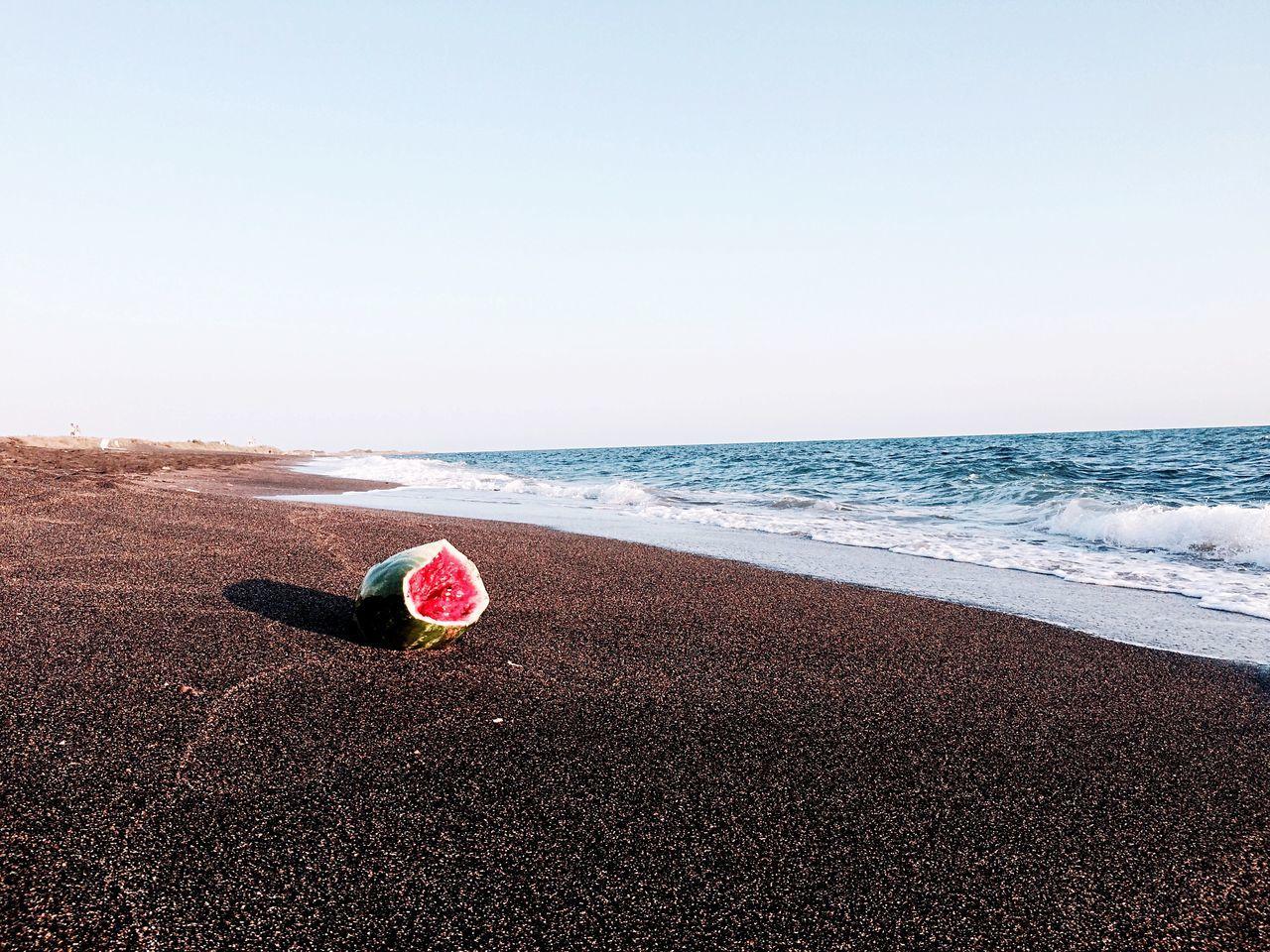 Abandoned watermelon on beach against clear sky