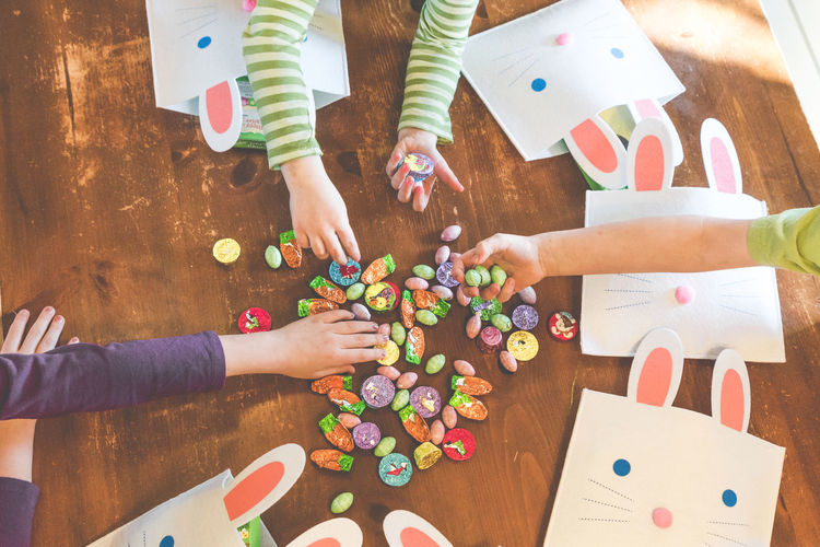 Cropped Image Of Children Holding Easter Candies On Wooden Floor
