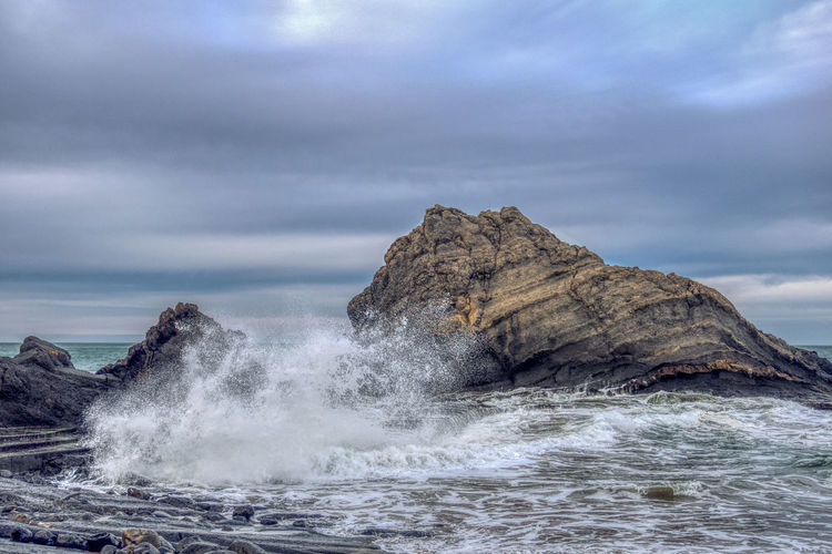 Rock formation hit by waves in sea against sky