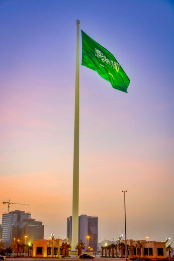 Low angle view of flag against sky at sunset
