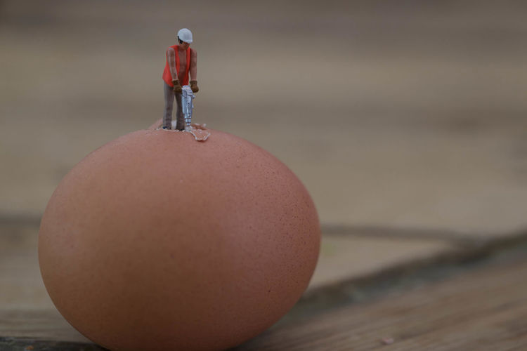 Figurine Of Jackhammer Drilling On Brown Egg