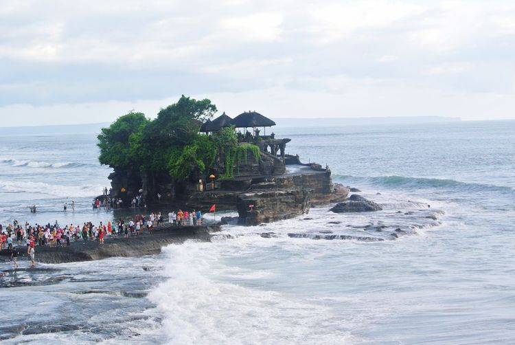 People at pura tanah lot in sea against sky