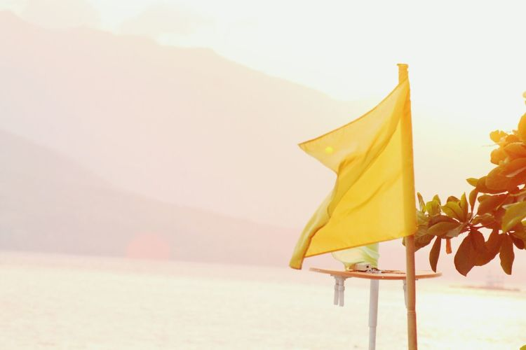 Scenic view of yellow flag against mountains