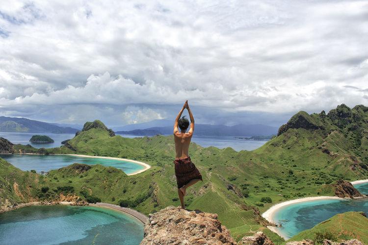 Rear View Of Man Performing Yoga While Standing On Rock Against Sky