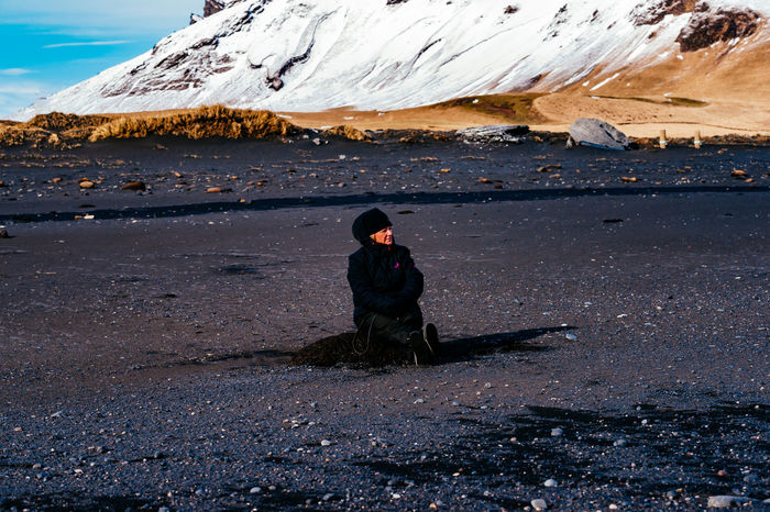 Beauty In Nature Casual Clothing Full Length Iceland Island Landscape Leisure Activity Lifestyles Mountain Nature Person Rear View Rock - Object Sitting Sky Standing Tranquil Scene Tranquility Warm Clothing Young Adult