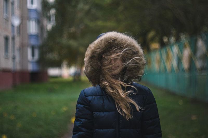 Girl in fur coat standing outdoors