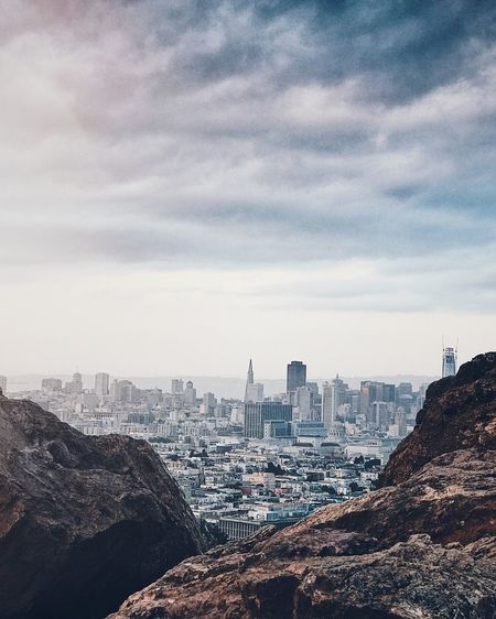 Cityscape seen from mountain against cloudy sky