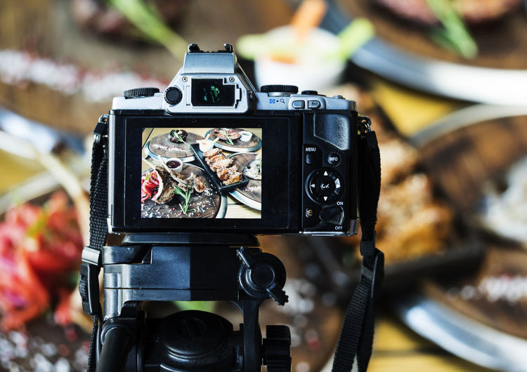 Close-up of camera photographing food served on table