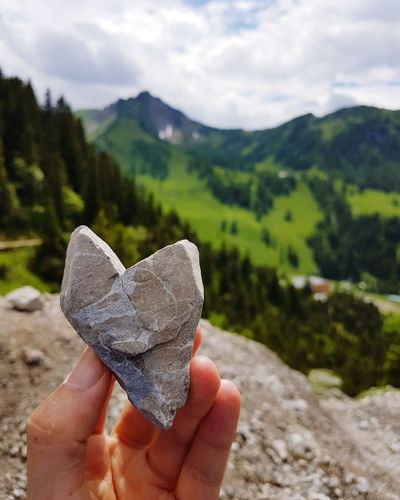 Close-up of person holding stone against mountain