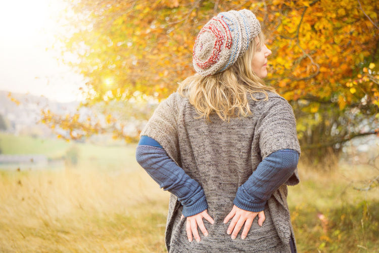 Woman stretches the back in autumn scenery Autumn Backside Cardigan Fashion Leafs Woman Atmospheric Autumn Foliage Autumn Scenery Back Pains Blond Hair Carelessly Chilly Colour Mood Comfortable Clothes Cord Clothes Deciduous Forest Gymnastics Lens Flare Middle Aged Poncho Stretch Stretches Herself Warm Clothes Warm Colours