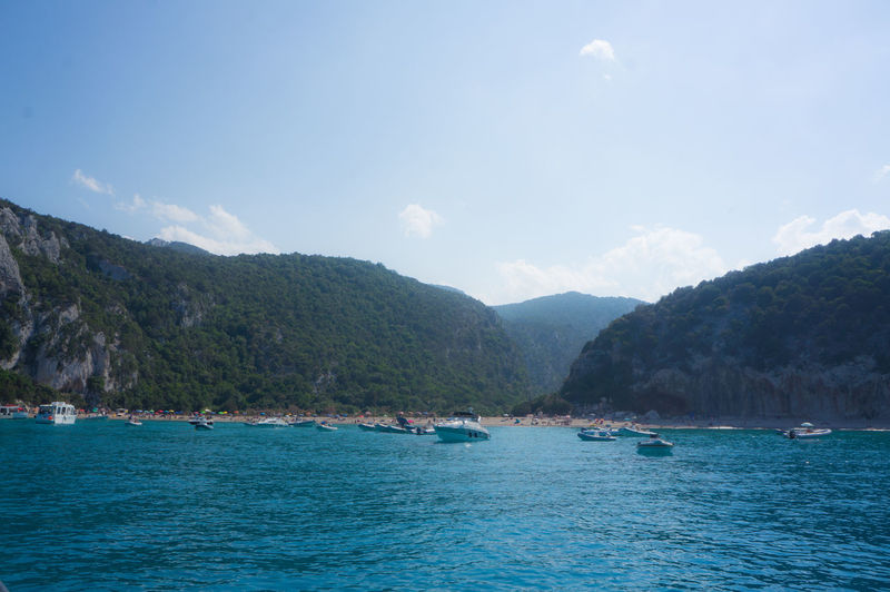 Boats On Mediterranean Sea By Mountains Against Sky At Cala Goloritze