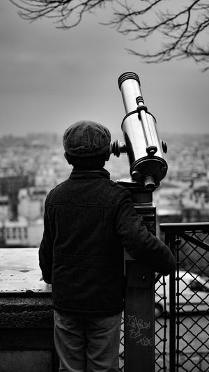 Rear view of boy standing by coin-operated binoculars