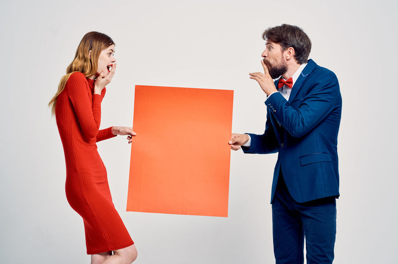 Young couple standing against white background