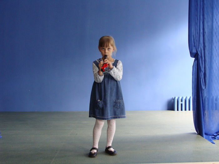 Full Length Portrait Of Girl Playing Flute Against Blue Wall