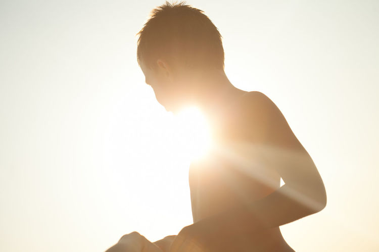 Silhouette shirtless boy against bright sky