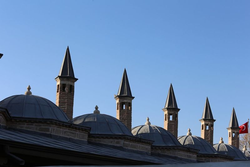 Dervish apartment dome roofs $ chimneys at the Mevlana Museum in Konya. The museum is the mausoleum of Jalal_ad-Din_Muhammad_Rumi also known as Mevlana or Rumi a Persian Sufi mystic. It was also the dervish lodge (tekke) of the Mevlevi order, better known as the whirling dervishes. It is one of the most famous Dervish lodges in the world. Architecture Building Exterior Built Structure Sky Religion Place Of Worship Building Clear Sky Belief Spirituality Travel Destinations Nature Dome Blue City Low Angle View Travel Copy Space No People Spire