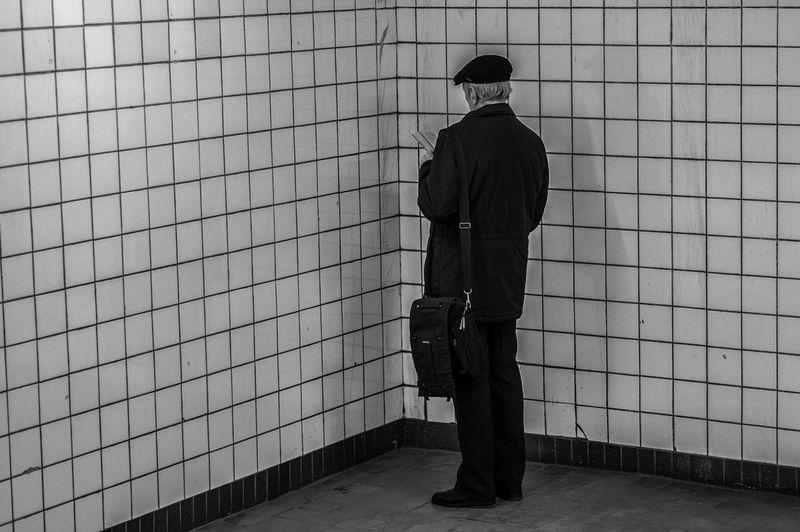 Man Reading Book In Corner Of Restroom