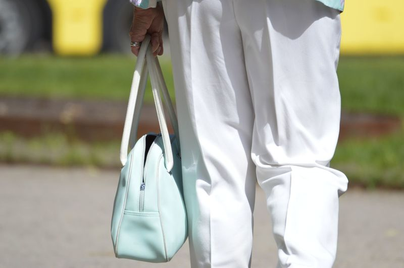 Woman holding purse while standing on footpath