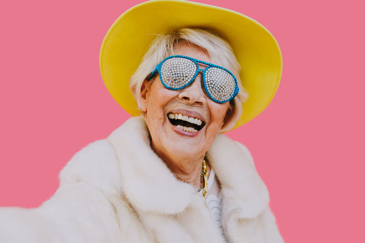 Portrait of cheerful senior woman wearing hat and sunglasses against pink background
