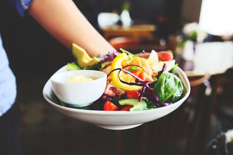 Cropped Image Of Waiter Holding Fresh Salad Plates At Restaurant